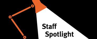 Lamp shining a spotlight on text that reads, staff spotlight